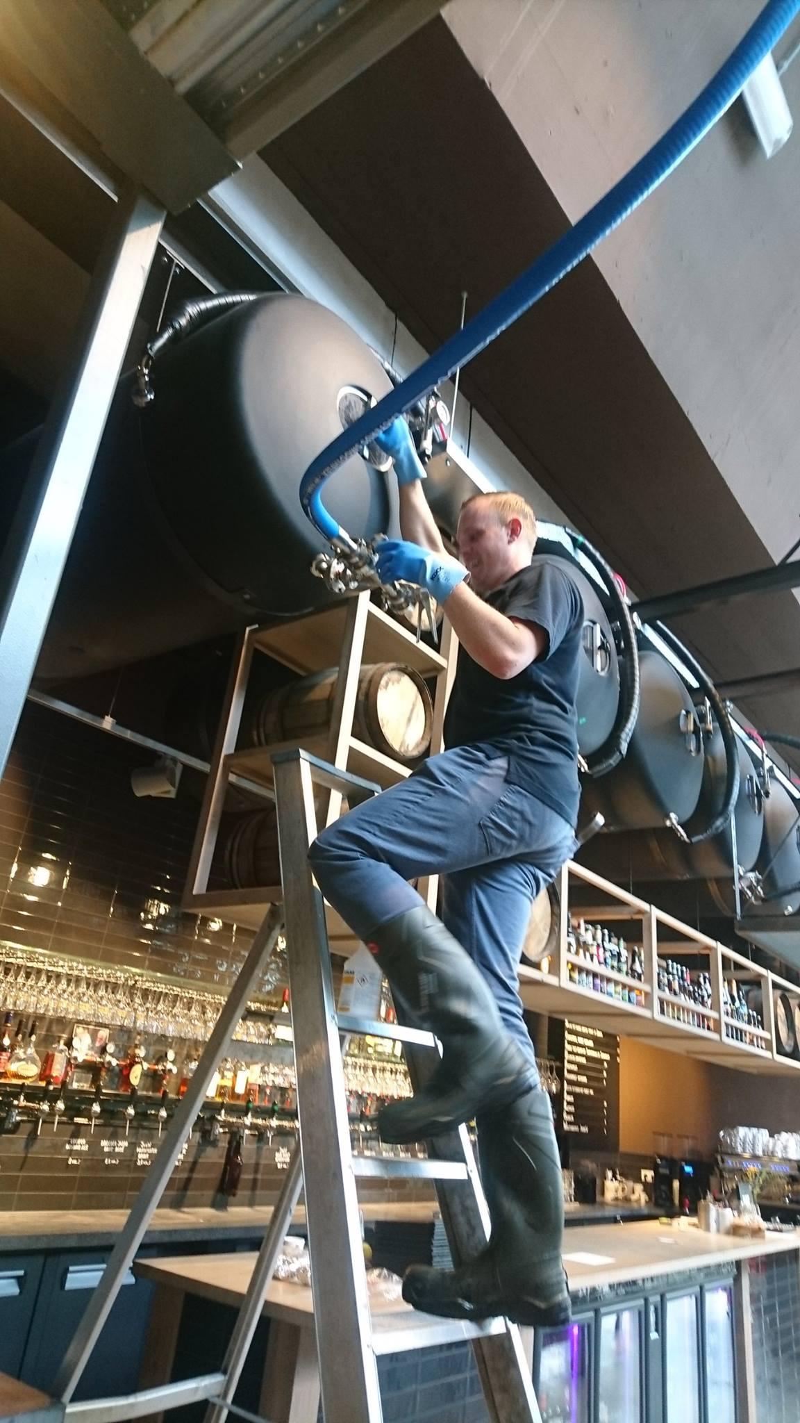 <p>Wesley Aarse vult een biertank boven de bar (2017)</p>